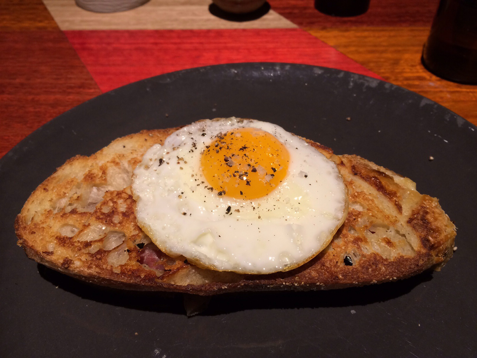 Bikini tostada, jamón serrano, and manchego on sourdough with a fried egg. Image courtesy of Bron.