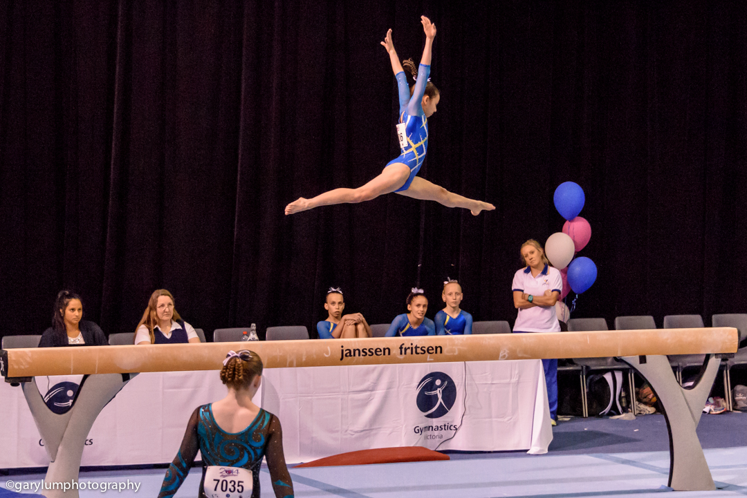Miss13 leaping from the balance beam NIKON D810 with 28.0-300.0 mm f/3.5-5.6 at 82mm and f/5, 1/500sec, ISO 8000