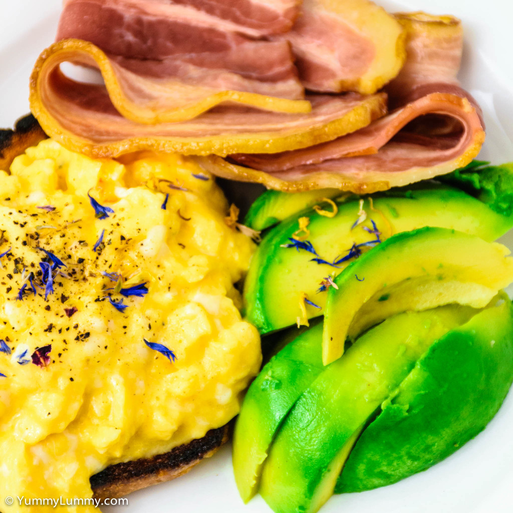 Streaky bacon and scrambled eggs with fried toast and avocado