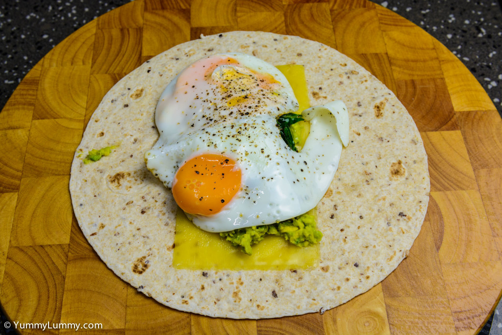 Helga's flatbread wrap with cheese, avocado, spinach and chard, and fried eggs