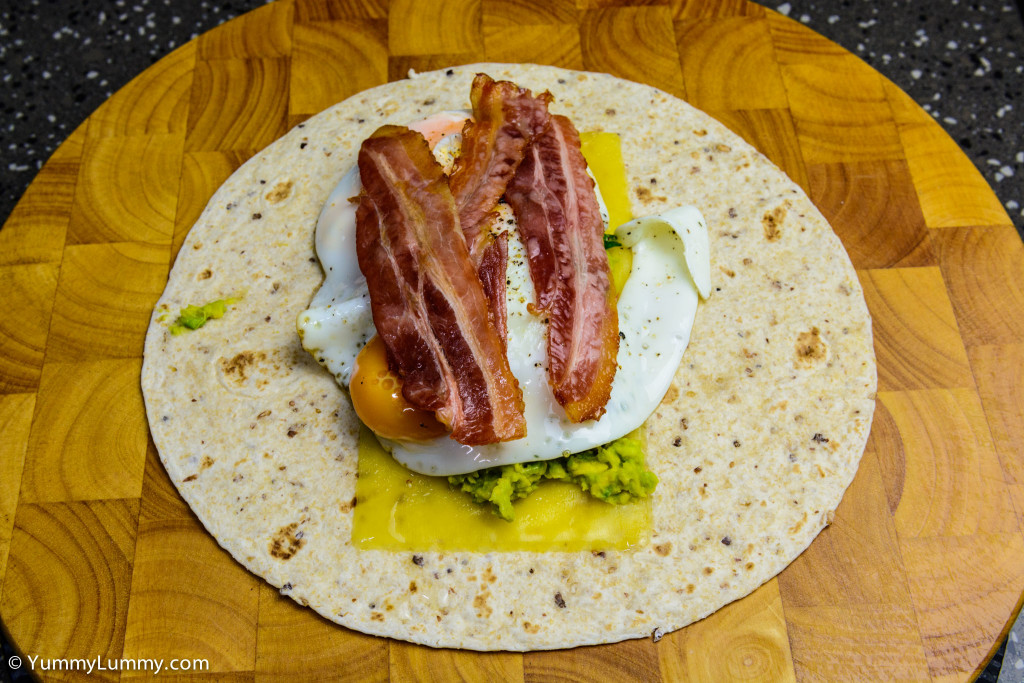 Helga's flatbread wrap with cheese, avocado, spinach and chard, fried eggs and streaky bacon