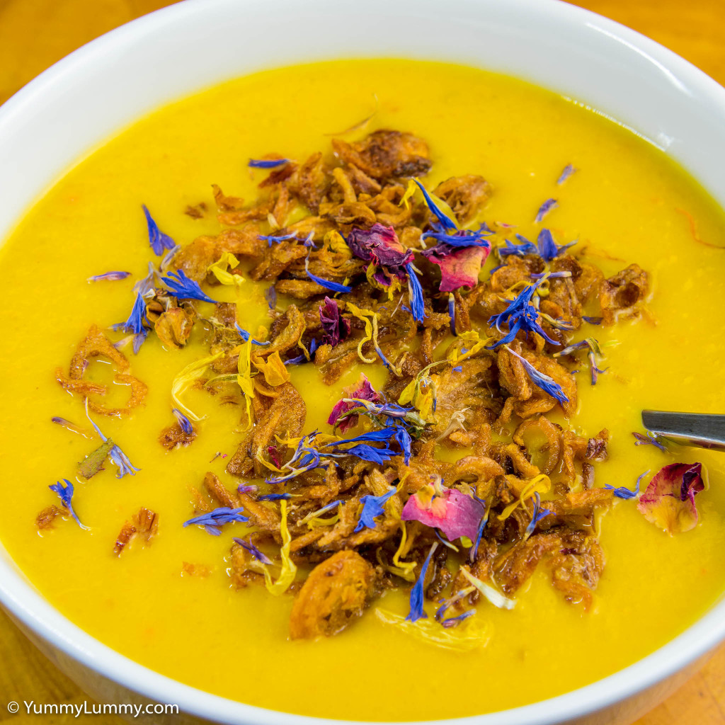 Hot and spicy pumpkin soup garnished with fried shallots and dried edible flowers