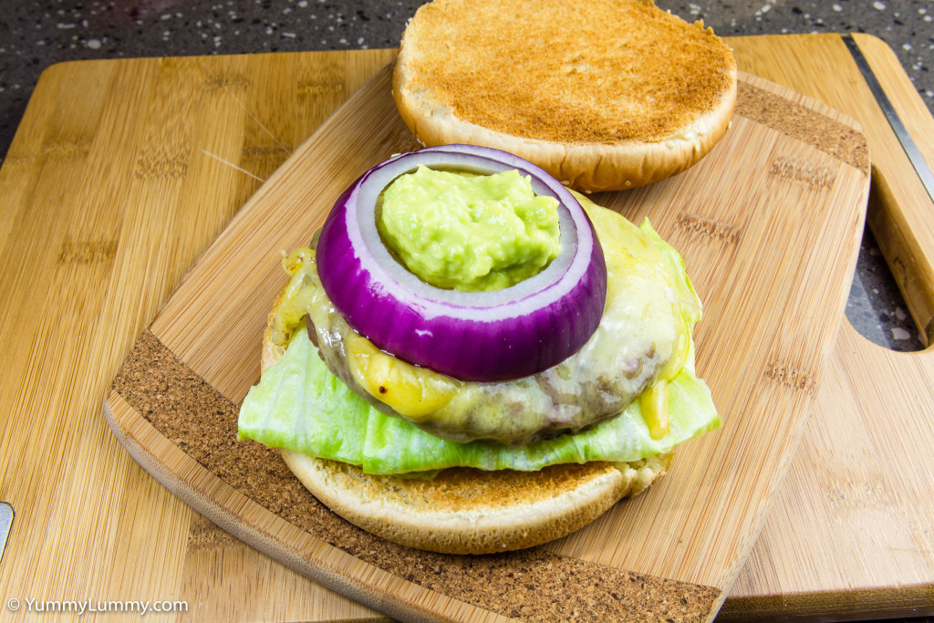 Hot and spicy jalapeño avocado on the bread roll with iceberg lettuce and beef burger topped with Coon cheese and onion rings
