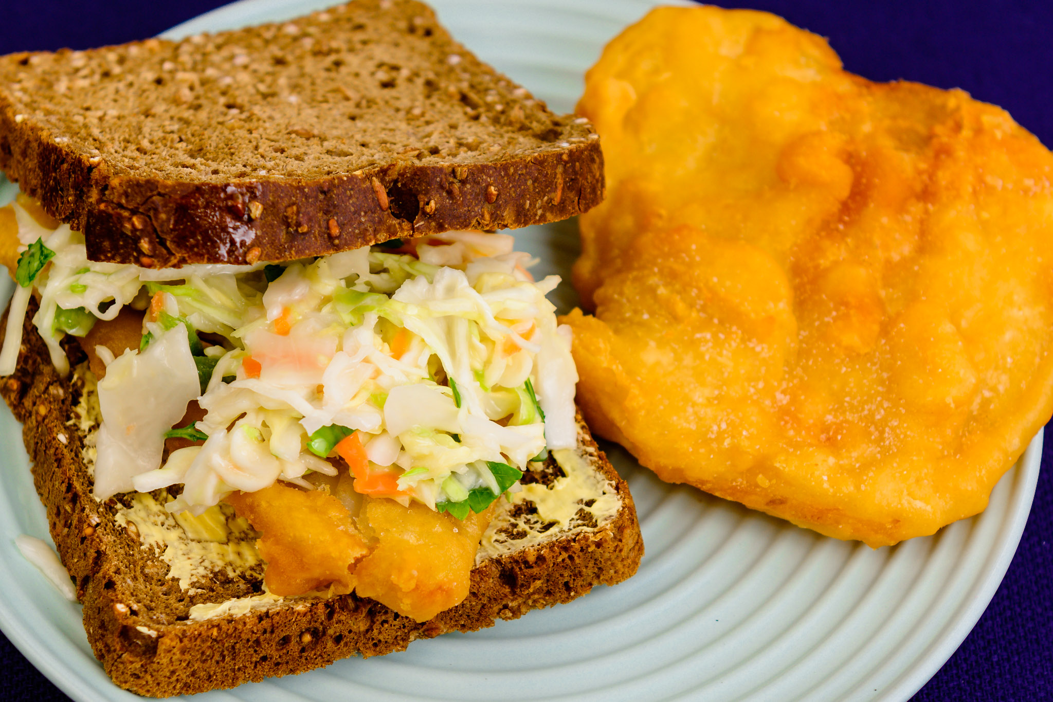 Payday dinner. Fish and coleslaw sandwich on rye bread with potato scallop.