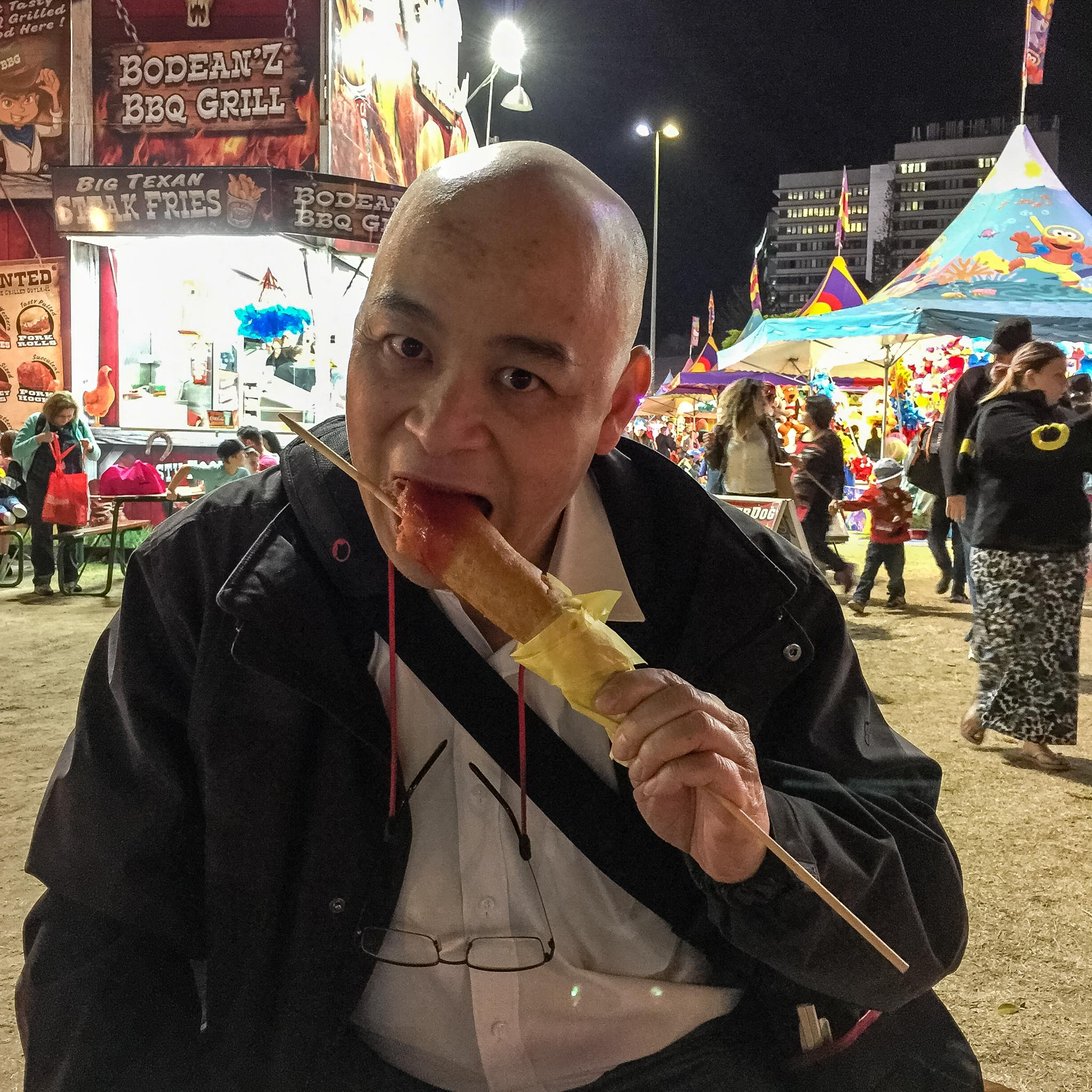 Gary Lum eating a Dagwood dog at The Ekka
