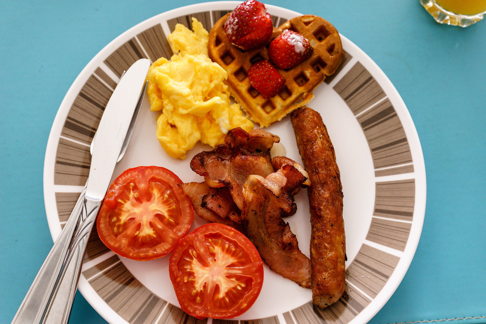 Sunday breakfast in Brisbane. Bacon, sausage and egg with waffle and strawberries and tomato.