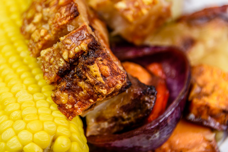 Saturday dinner. Pork belly with vegetables and sweet corn. Close up of crackling.