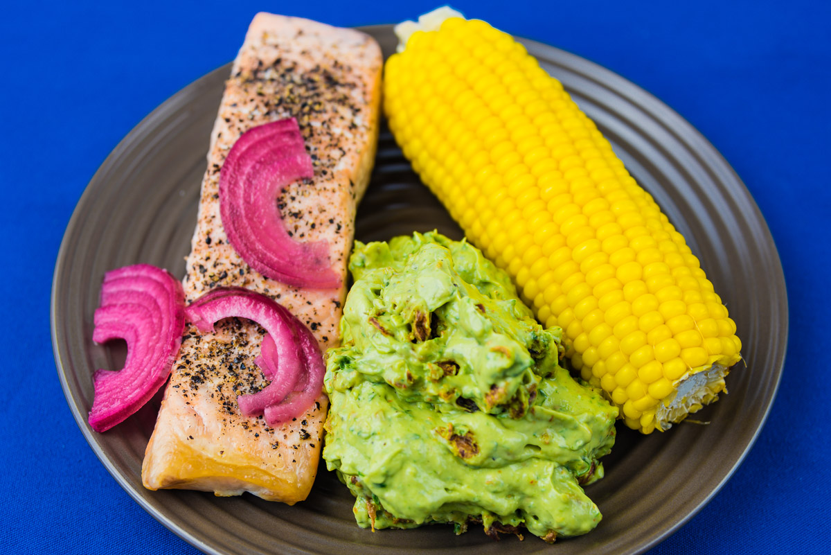 This is a photograph of Monday dinner. Baked salmon, sweet corn and wasabi aioli avocado.