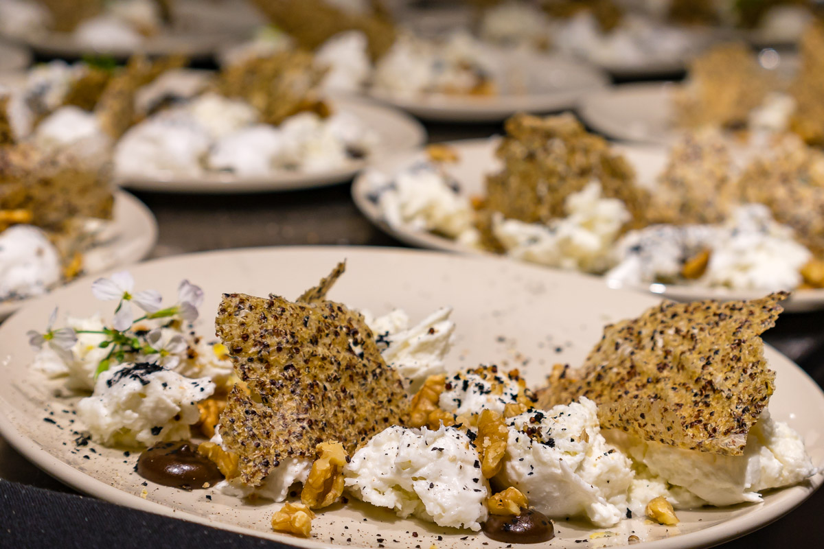This is a photograph of an entrée plate of Shaw River buffallo mozzarella, black garlic, smoked walnuts, quinoa