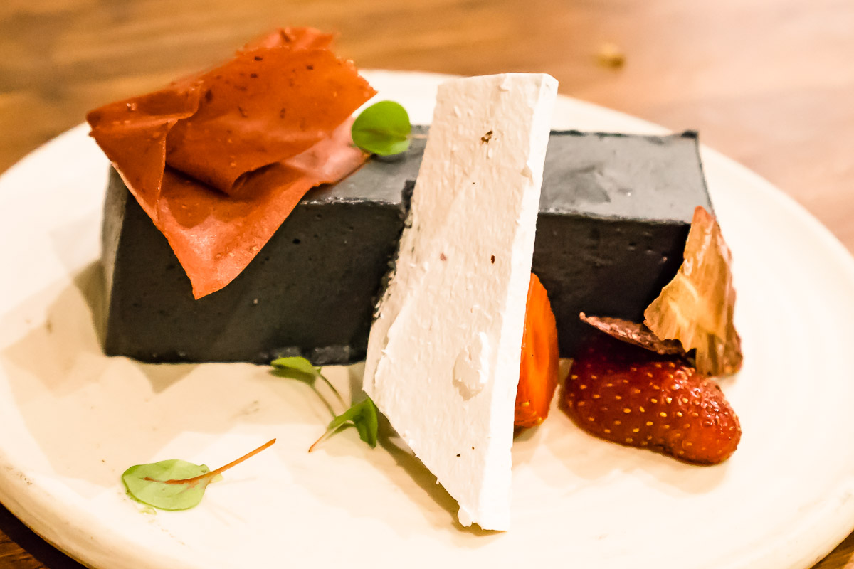 This is a photograph of dessert, a Black sesame bavaro is, strawberries, pink peppercorn meringue, sorrel at A. Baker