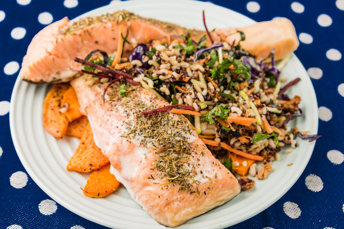 This is a photograph of Baked salmon with sweet potato chips, quinoa rice and kale coleslaw