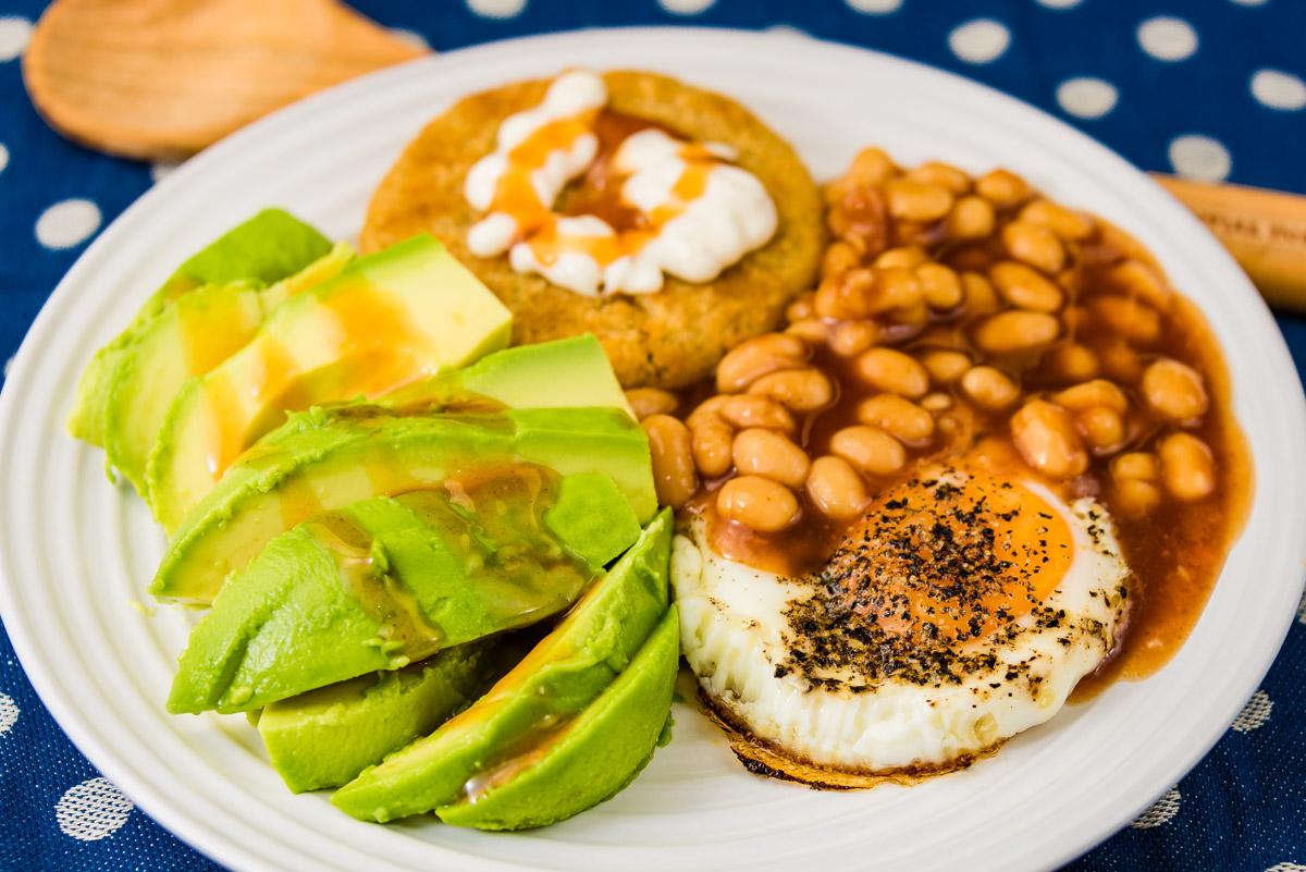 This is a photograph of Saturday lunch. Salmon rissole with fried egg, baked beans and avocado.