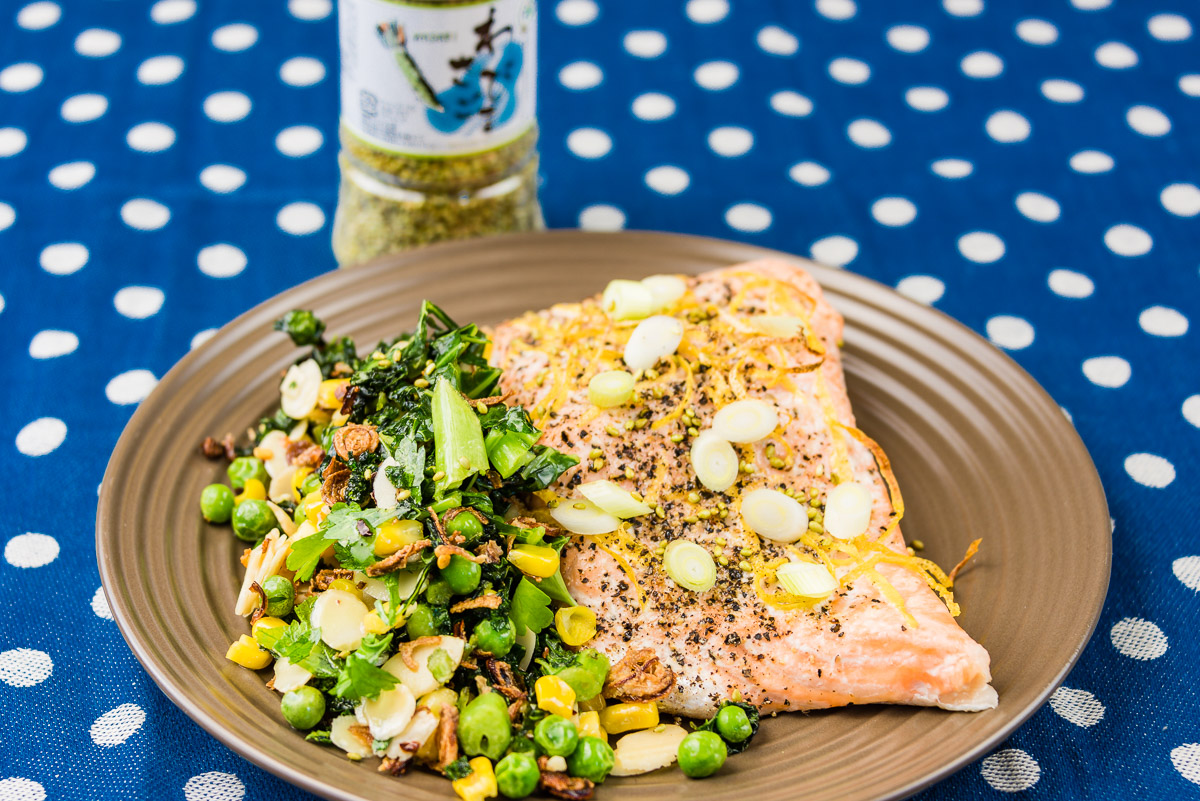 Baked salmon with wilted kale, peas, corn, almonds, shallots, spring onions, lemon zest, chilli flakes and wasabi sesame seeds