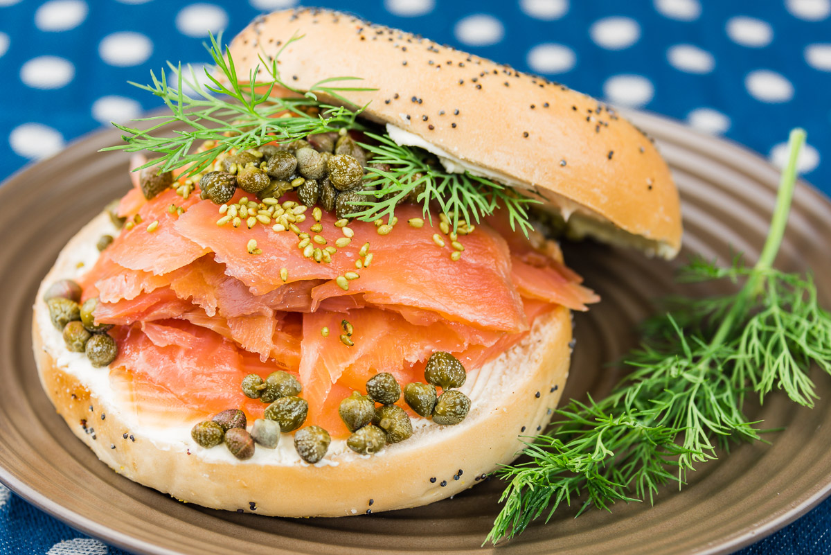 This is a photograph of a Smoked salmon, cream cheese and capers on a poppy seed bagel