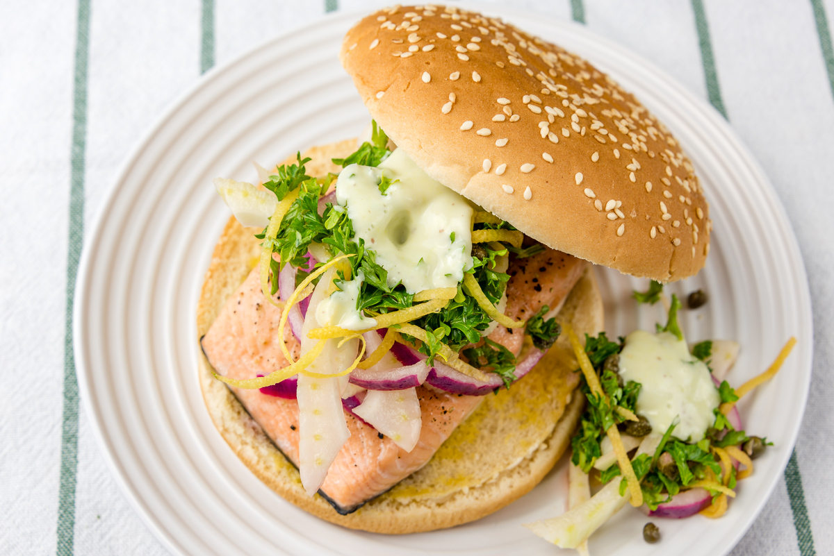 This is a photograph of Baked salmon with fennel salad and wasabi aioli burger