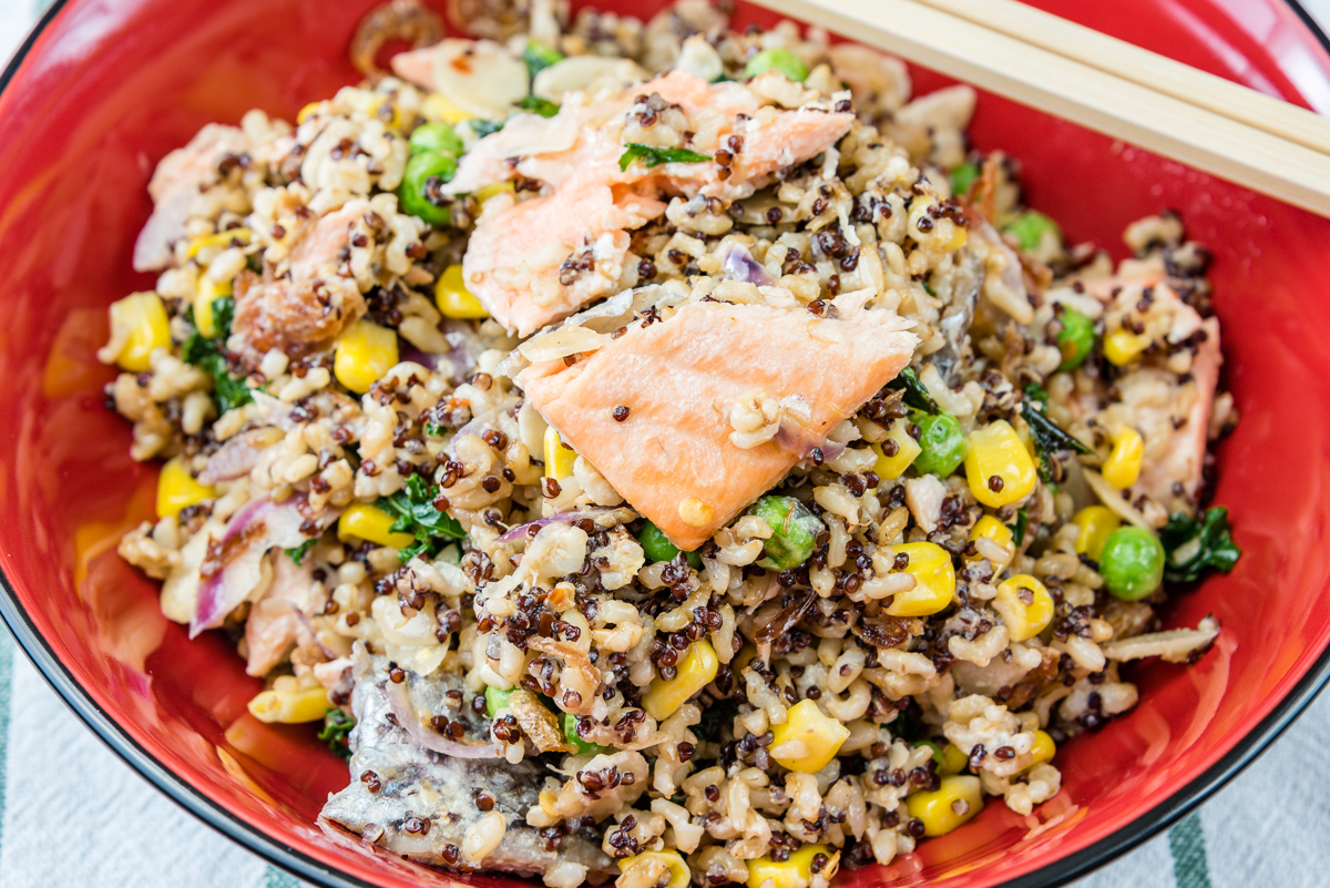 This is a photograph of Fried brown rice with red quinoa and salmon and kale