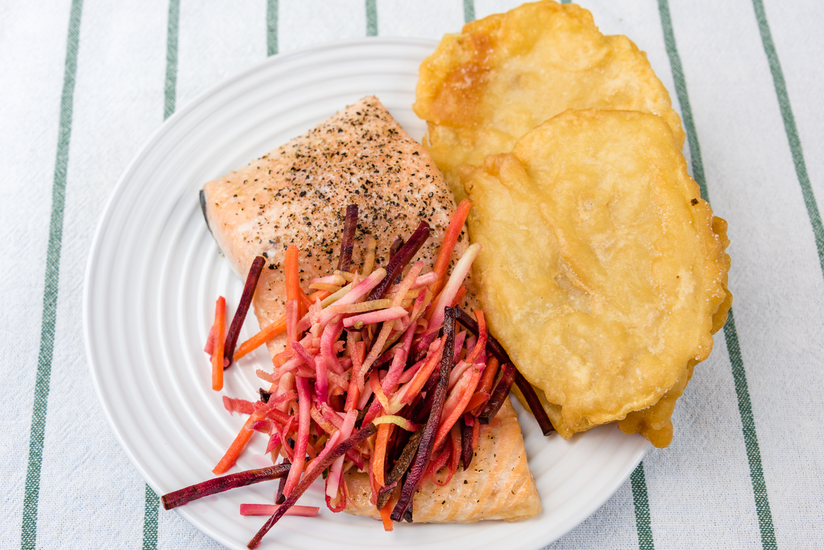 This is a photograph of Baked salmon with pickled coleslaw and potato scallops