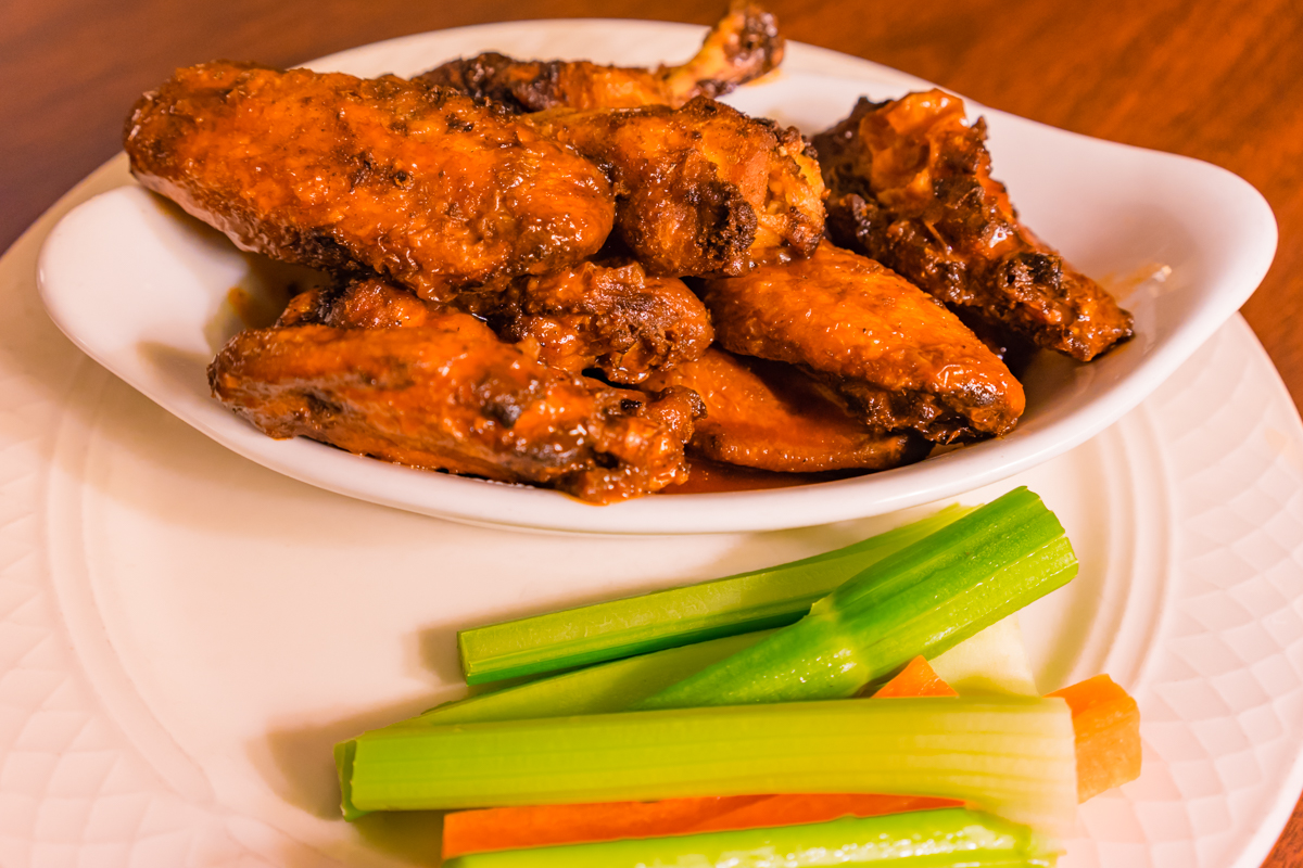 Photograph of Chicken Wings baked fried and chargrilled jerk seasoned wings tossed in buffalo barbecue sauce