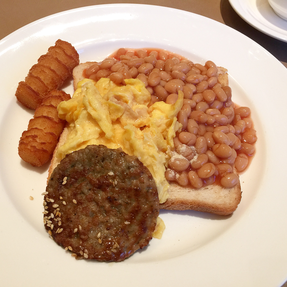 Toast with scrambled eggs and baked beans with a hamburger rissole and deep fried potato