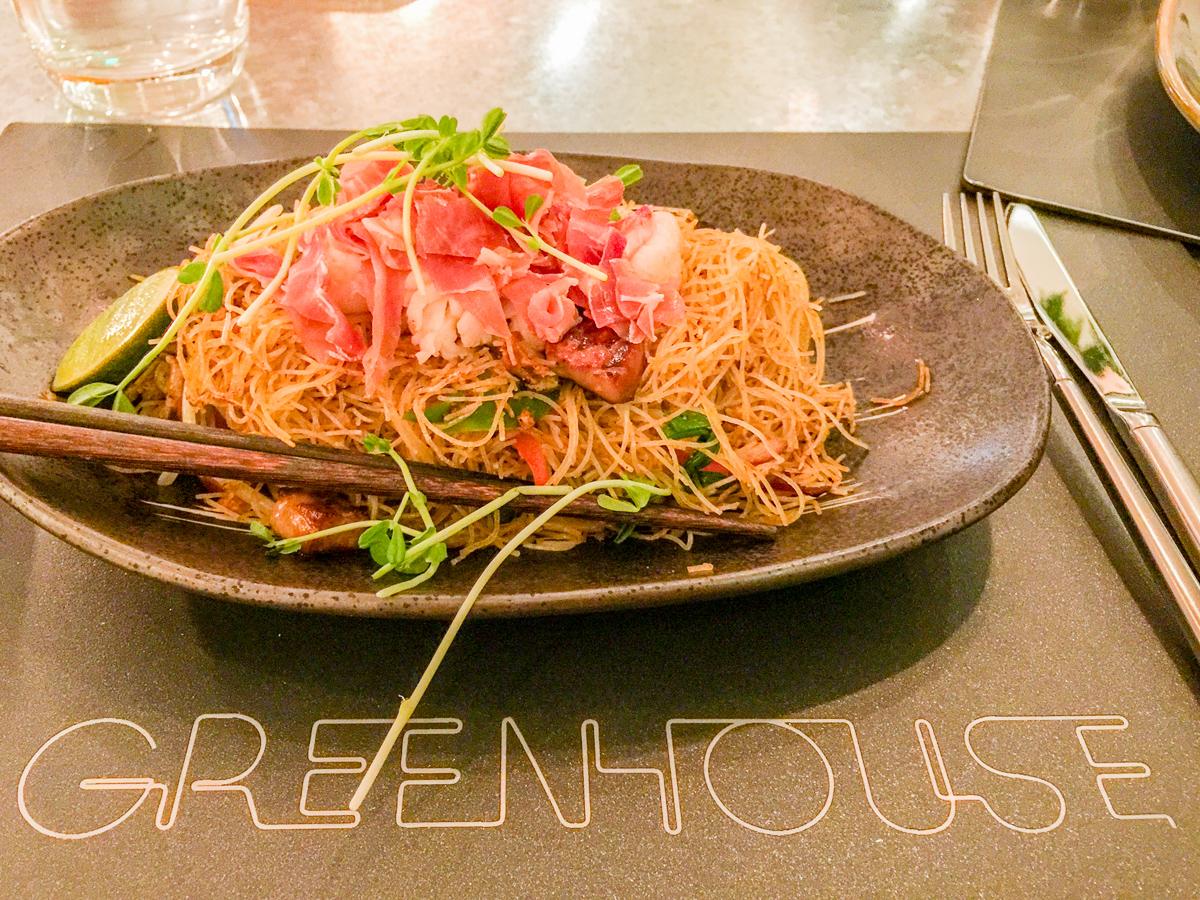 A photograph of a plate of Singapore noodles with lobster and bacon from Greenhouse