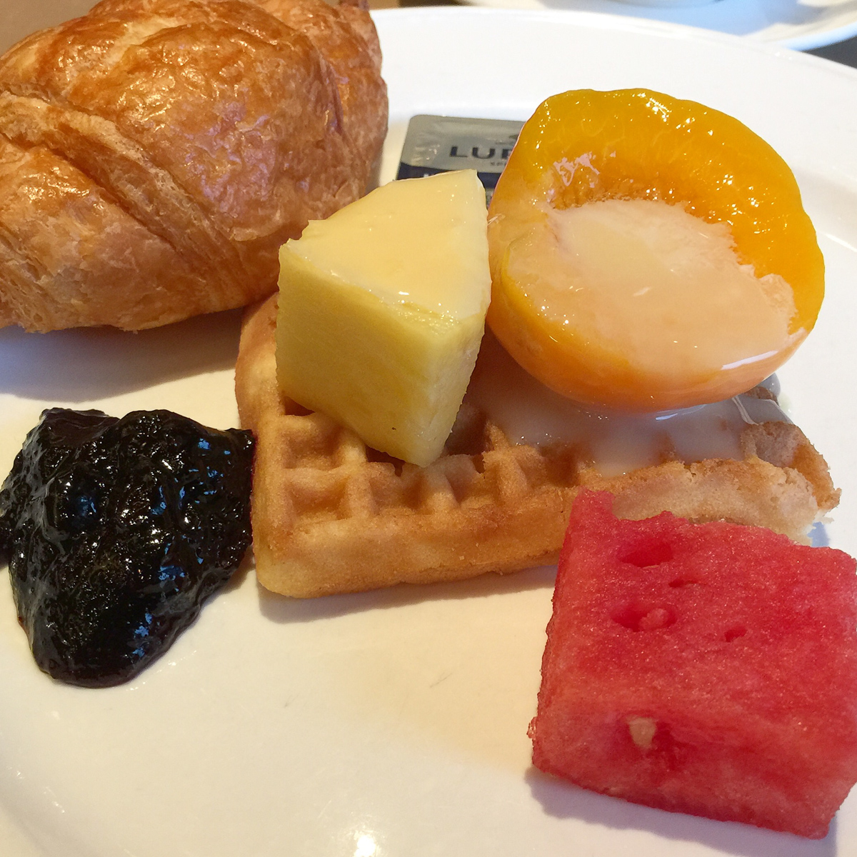 A photograph of Breakfast waffle with fruit, jam, condensed milk and a croissant