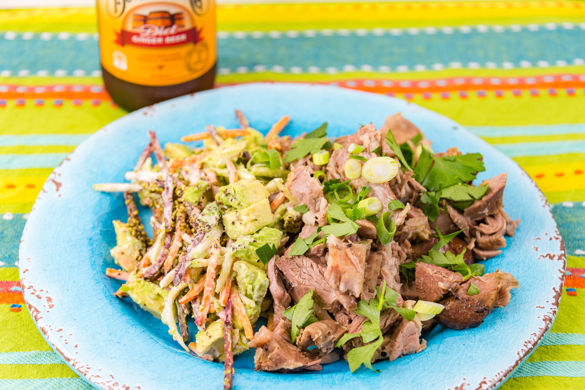A photograph of Leftover roast lamb and coleslaw with avocado with a bottle of Bundaberg ginger beer in the background.