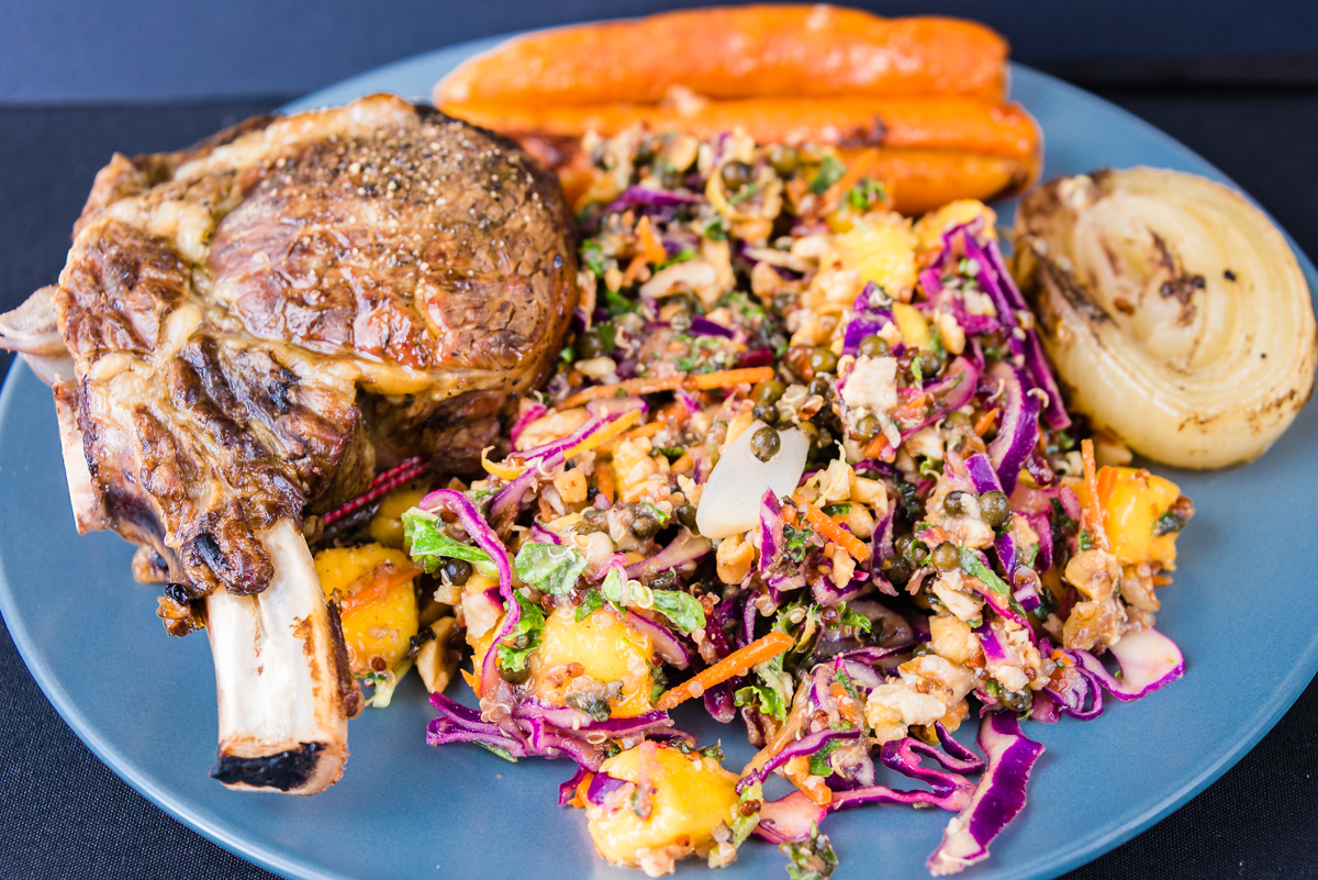 Standing rib eye roast beef with mango, quinoa, kale and nut coleslaw served with carrots, onion and green peppercorns