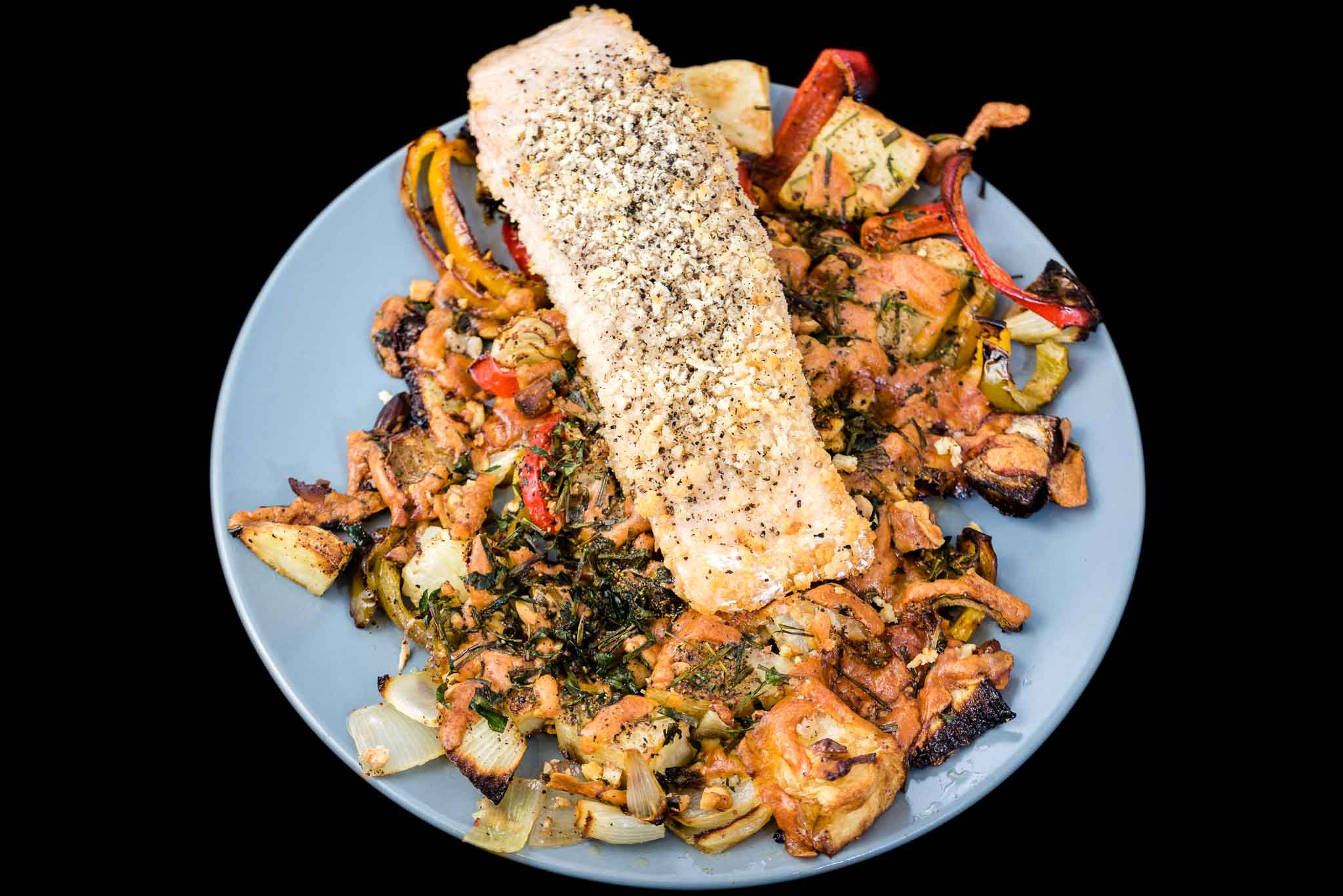 Baked panko crusted salmon with cheesy roasted red, green and yellow capsicums, onion, potato and cheese with chives and parsley