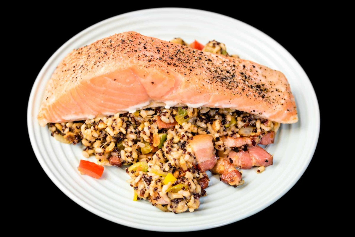 Baked salmon with fried quinoa rice and capsicum, onion, crushed nuts, cheese and speck