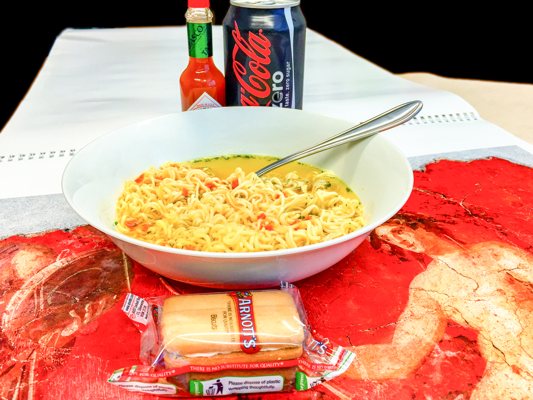 Chicken noodles with Tabasco sauce plus a biscuit and a can of Coke