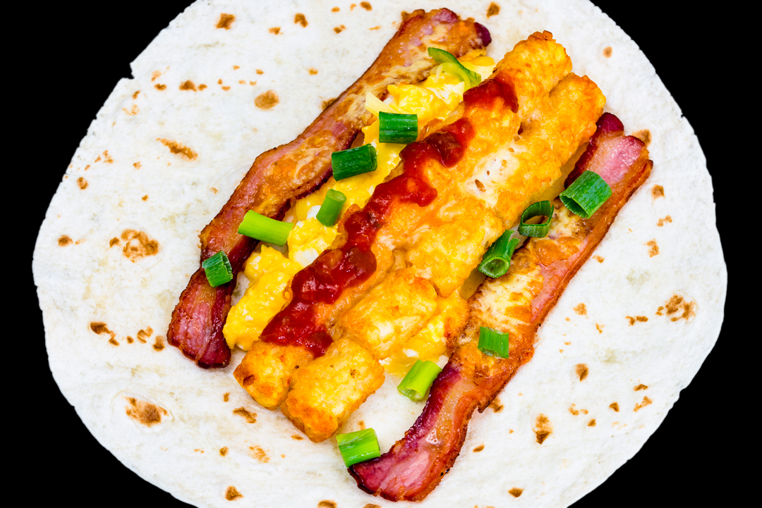 Breakfast tortillas with scrambled eggs, bacon, potato gems, salsa, cheese and spring onions