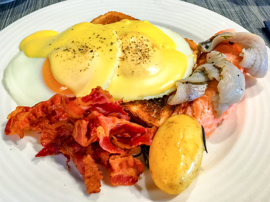Pickled herring, smoked salmon, poached eggs, with Hollandaise sauce plus crispy bacon and potato on buttered toast