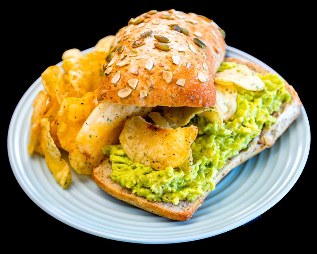 Smashed avocado on pumpkin seed roll with black pepper and lime chips and balsamic vinegar