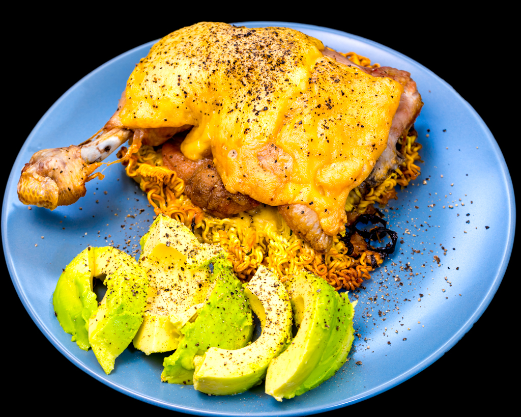 Baked cheesy chicken Maryland on a bed of crispy noodles with chilli chives and avocado