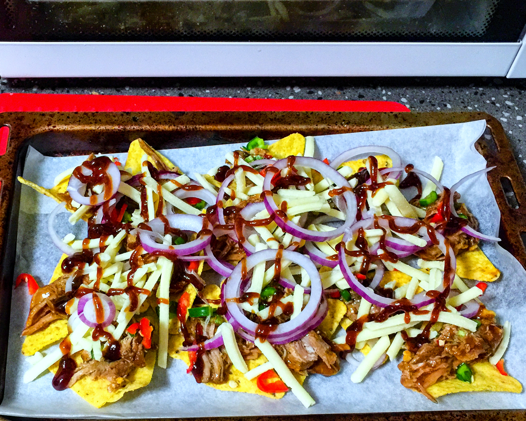 Leftover pulled pork nachos with Coon cheese, chillies, red onion, chives and barbecue sauce ready for the oven