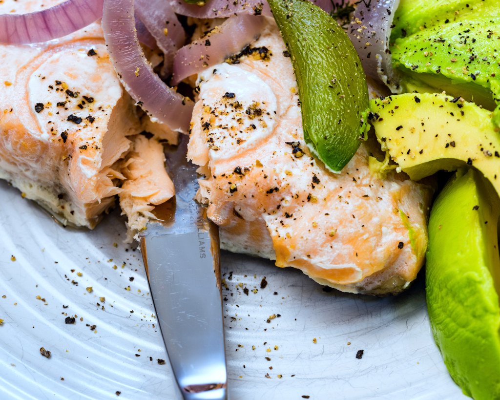 Salmon cooked in paper with sugar snap peas and onion served with avocado