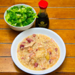 Ham hock and chicken thigh congee served with shredded lettuce and soy sauce Gary Lum
