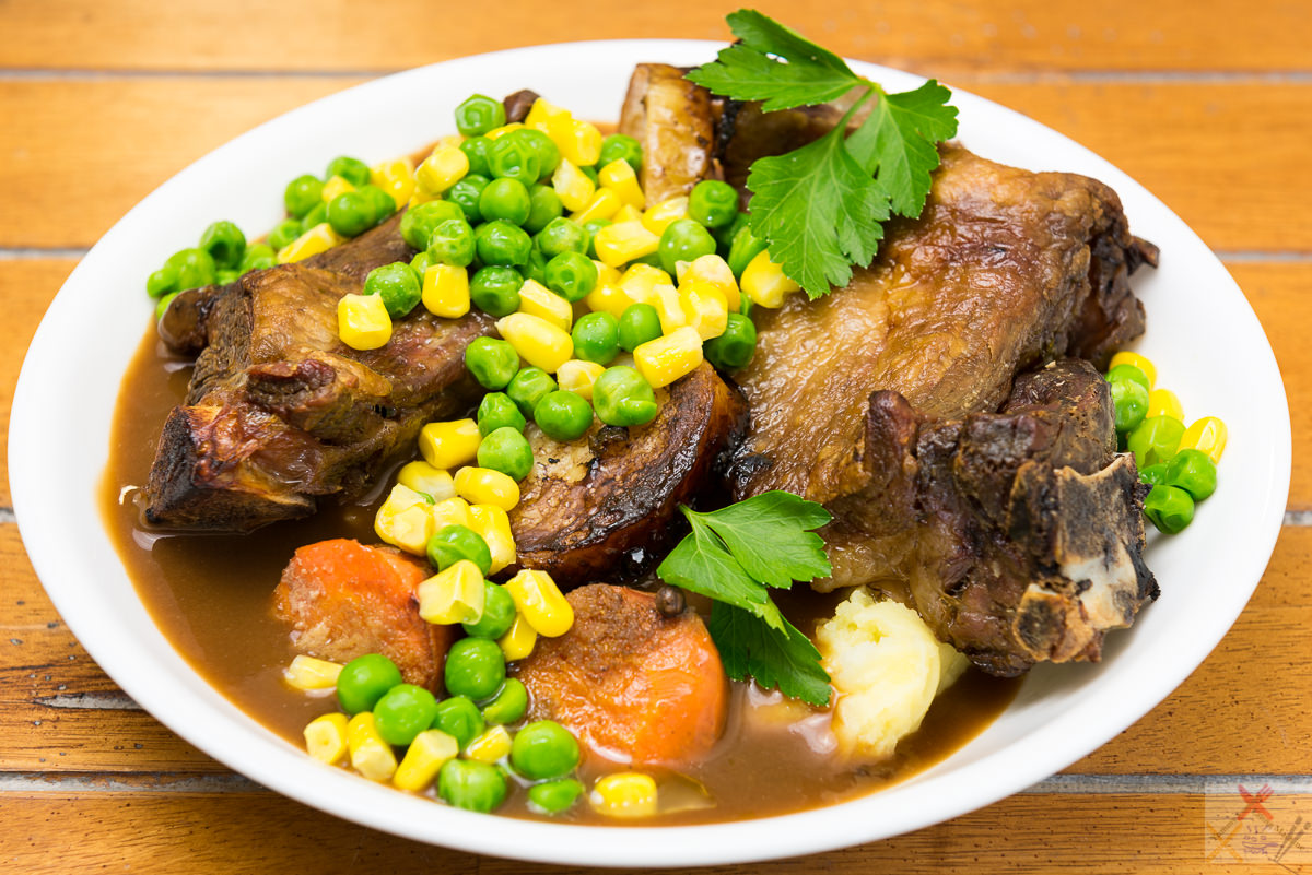 Slowly roasted lamb bones served with mashed potato, peas, corn and carrot with gravy Gary Lum
