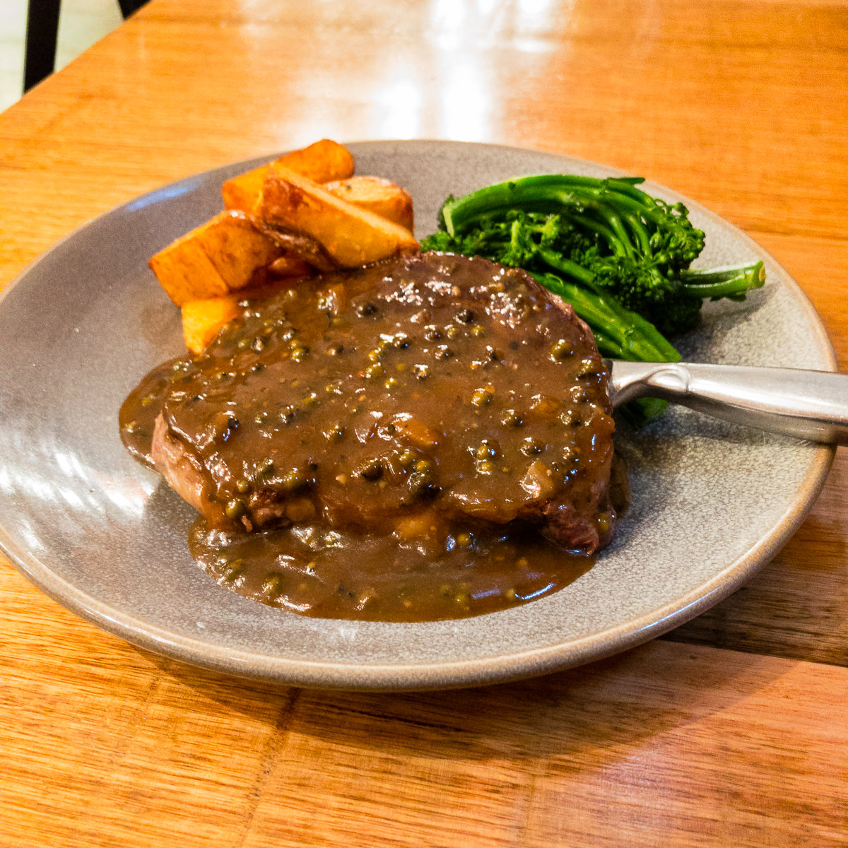 Scotch fillet steak with peppercorn sauce served with chips and broccolini Gary Lum