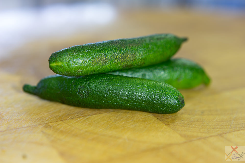 This is a photograph of three Australian finger limes arranged on a cutting board.